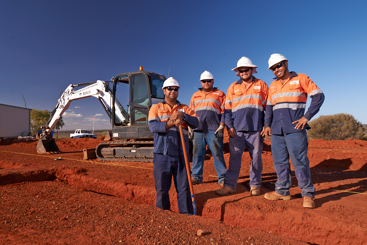Intract contractors posing at construction site in front of excavator