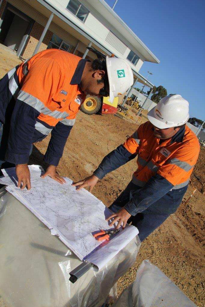 Intract contractors looking at blueprints at construction site