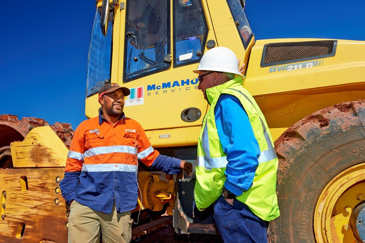 Intract Services contractors and leaders discussing job infront of construction equipment