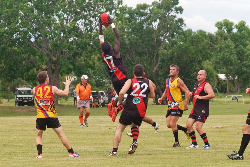 Jabiru Bombers players mid match, player jumping and catching ball